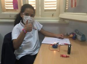 Schülerin mit Stromkreis und Heft